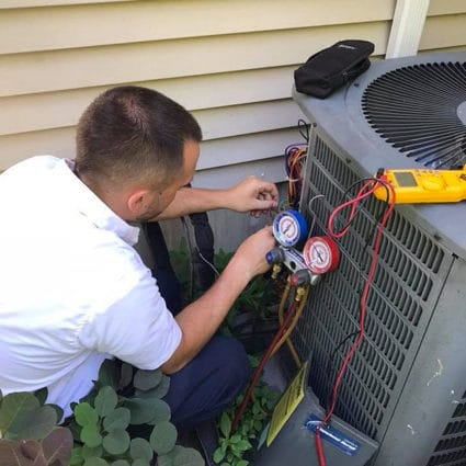 A Reimer technician inspects an AC condenser as part of our top AC tune-up in Buffalo, NY.