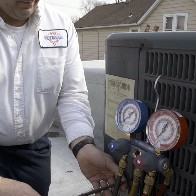 During an AC repair visit, our technician diagnoses the problem by checking the unit's refrigerant levels.