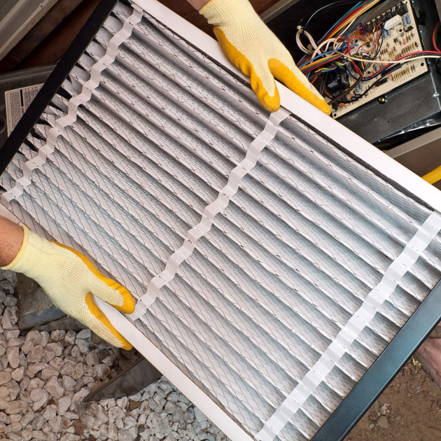 A Reimer technician inspects a home's HVAC air filter as part of our tune-up service.