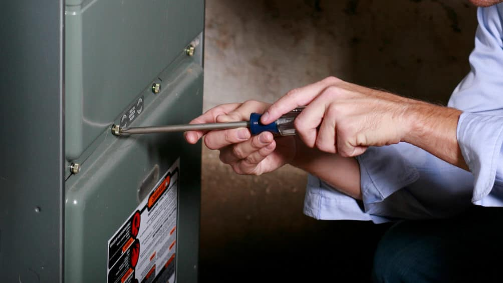 Our plumber uses a screwdriver to attach the faceplate of this gas furnace, completing its installation.