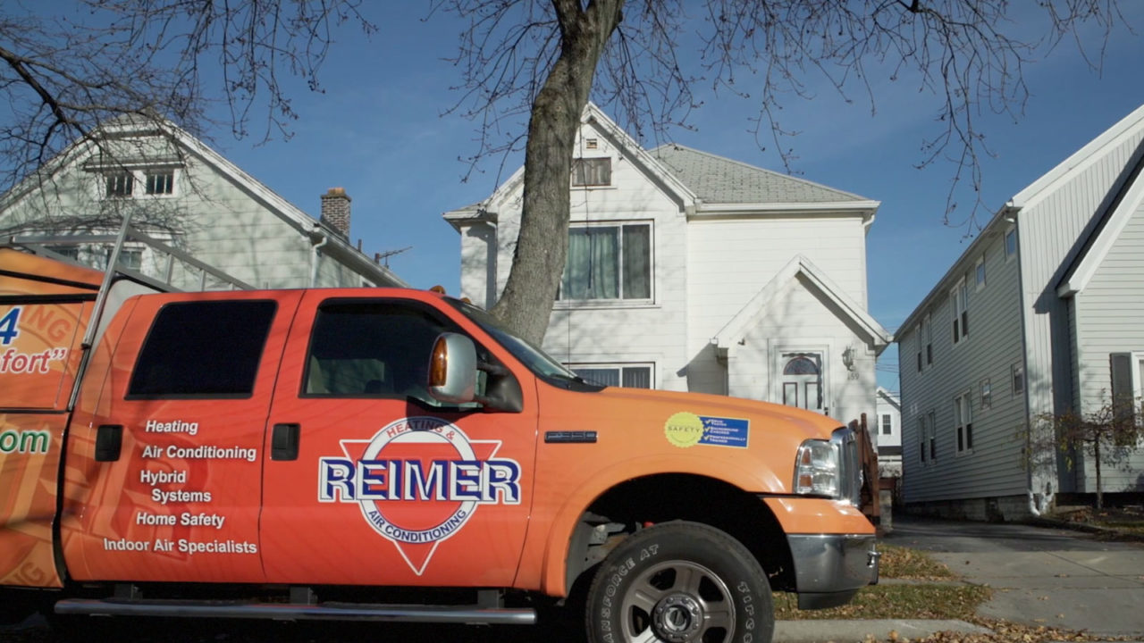 A Reimer service truck pulls up in front of a Buffalo home, with its tech ready to start on HVAC repairs.