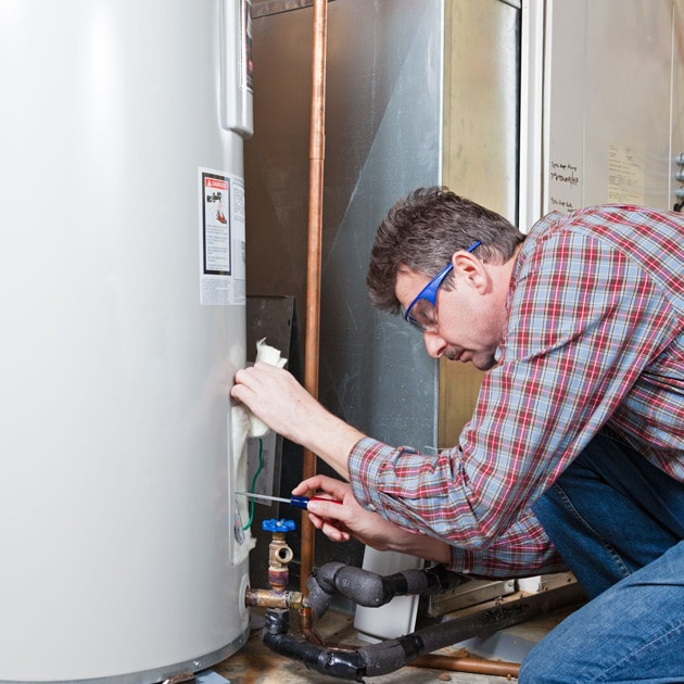 A Reimer plumber uses a screwdriver to finish up maintenance for this home's water heater.