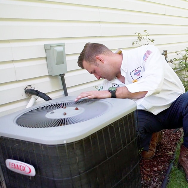 A Reimer technician in a white shirt, blue pants, and work boots fixes a local home's air conditioner here in Buffalo, NY.