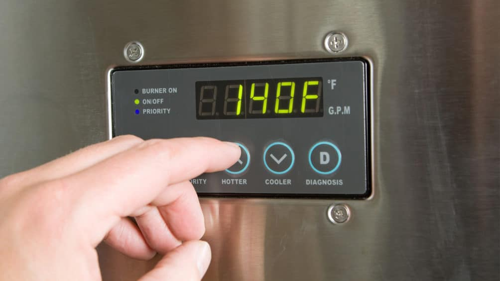 A Reimer plumber uses a control panel to adjust the temperature of this tankless water heater after installation.